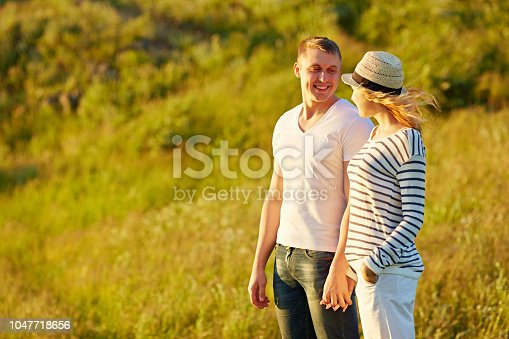 Portrait of young beautiful Caucasian couple holding hands and looking at each other with love while standing in the field on summer evening