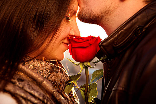 Amorous guy gently kissing his girl with red rose - foto de acervo