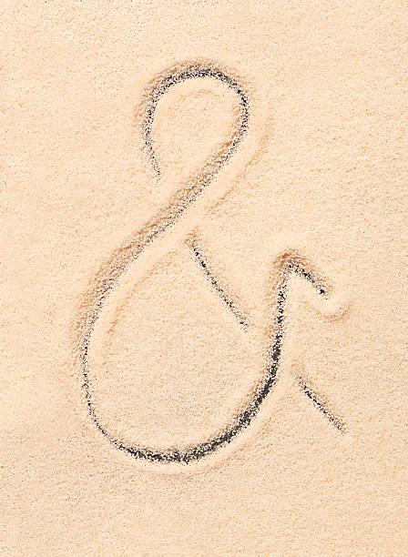 Ampersand symbol drawn on sand stock photo