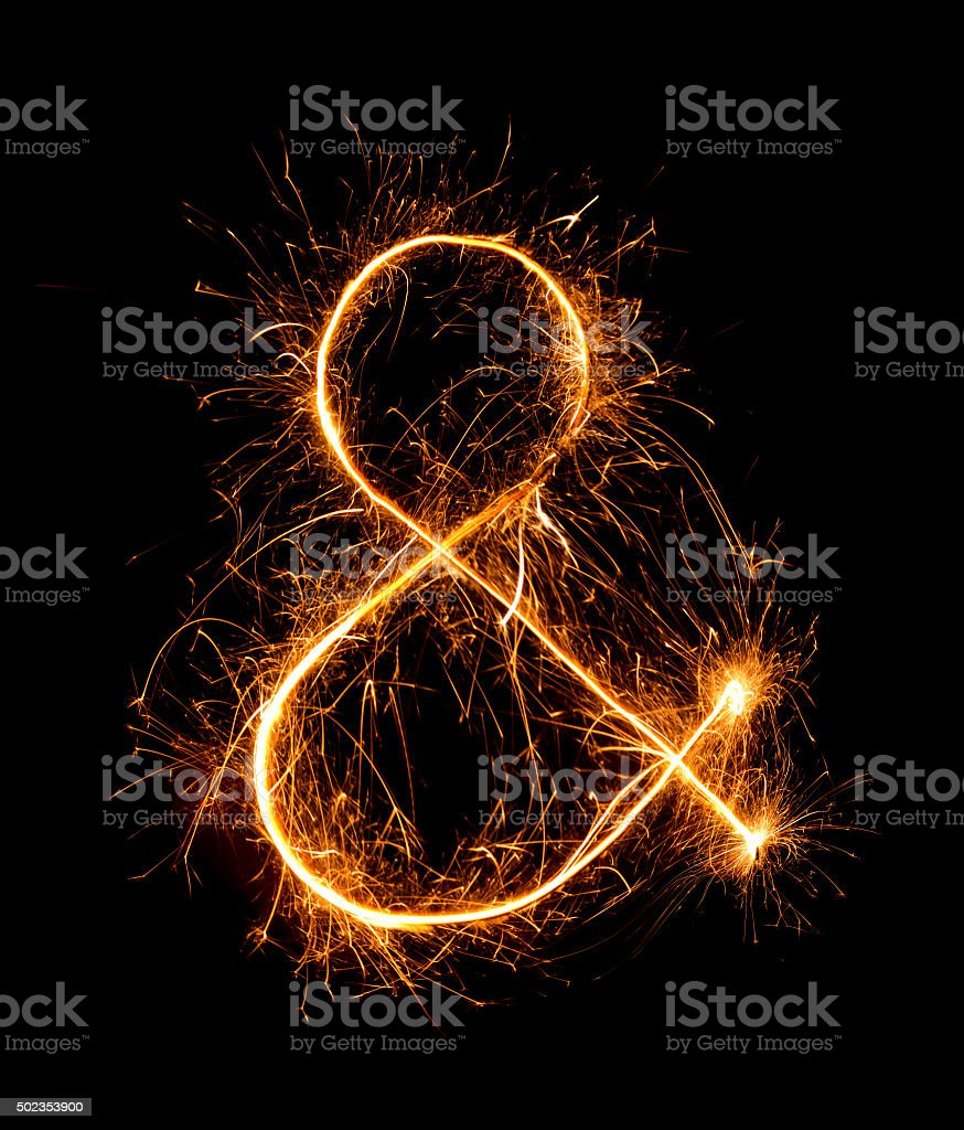 ampersand symbol  made of firework sparklers at night stock photo