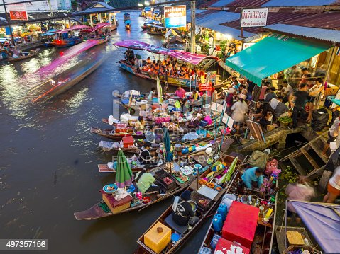 Samut Songkhram, Thailand - July 20, 2013: Boats lined along the river in Amphawa Floating Market as vendors and shop owners get busy with customers.