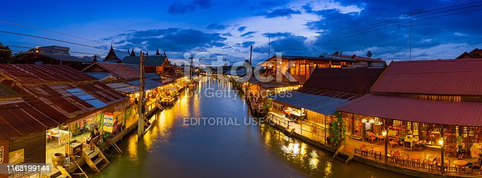Samut Songkhram, Thailand - 14 July 2019: Amphawa market canal, the most famous of floating market at sunset and cultural tourist destination on