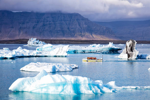 Amphibian Boat Trip on Jokulsarlon Glacier Lagoon, Iceland Amphibian boat trip on Jokulsarlon glacier lagoon, the tourists sailing among the huge icebergs in the picturesque scenery. Huge blocks of ice constantly break off the glacier, Breidamerkurjokull, and large icebergs float on the lagoon. jokulsarlon stock pictures, royalty-free photos & images