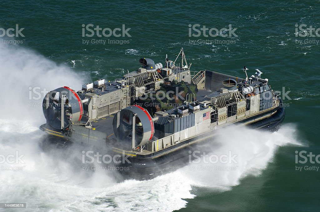 Amphibious military hover craft races towards shore stock photo