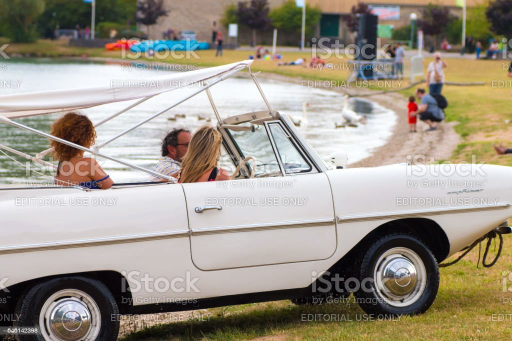 Amphicar model 770 amphibious automobile from 1960's on river in France with some tourists peacefully sailing in summer stock photo