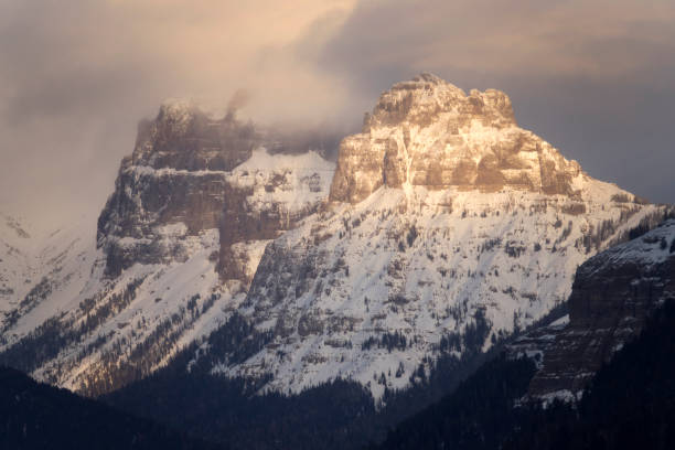 At sunset, stormy winter snow storms roll over Amphitheater Mountain in the Absaroka Mountains of Yellowstone National Park in Wyoming.