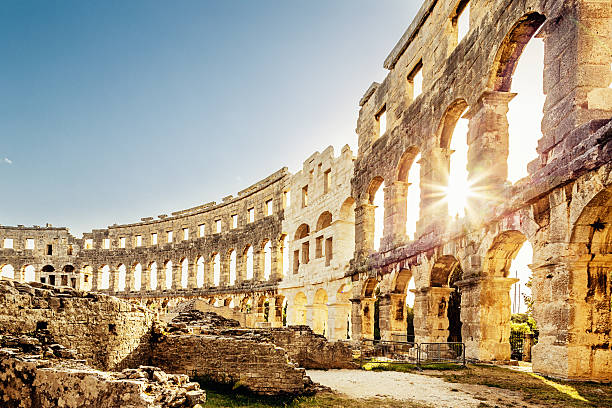 Amphitheater Pula,Croatia Landmark Roman Amphitheater in Pula Croatia. Built during 1st century AD, the amphitheater is the sixth largest in the world and has well preserved outer walls. Interior view with sun shining through arches into the roman colosseum. City of Pula, Croatia. amphitheater stock pictures, royalty-free photos & images