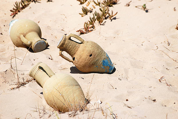 Amphoras lying in sand stock photo