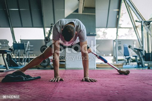 Amputee athlete with artificial leg, living the healthy lifestyle, exercising in the gym.