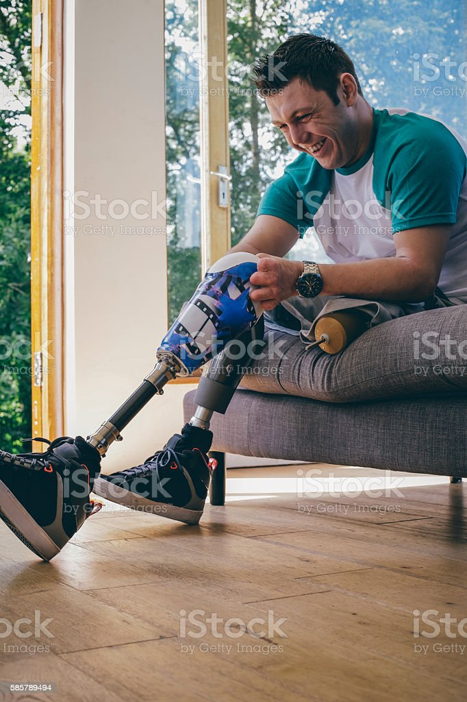 Amputee Attaching his Legs stock photo