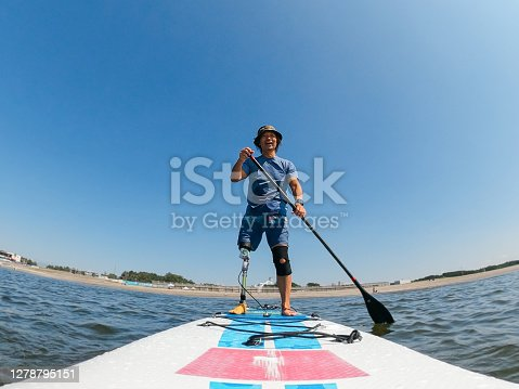 A font view of an amputee man paddle boarding in the sea.