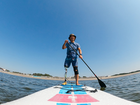 Amputee man paddle boarding in sea
