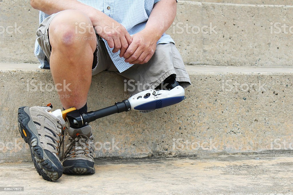 Amputee man seated with legs crossed stock photo