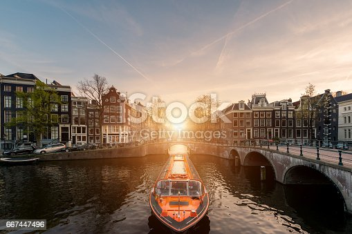 istock Amsterdam canal cruise ship with Netherlands traditional house in Amsterdam, Netherlands. 667447496