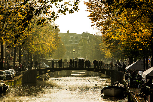 Amsterdam, Netherlands October 23 2019: Amsterdam canal with boats,bridge and people in autumn sunlight