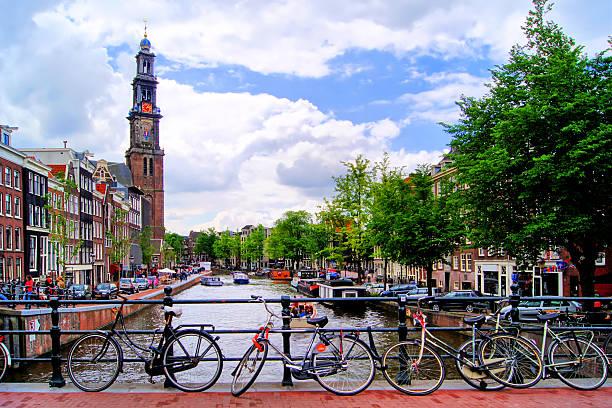 amsterdam canal scene with church and bicycles - westerkerk stockfoto's en -beelden