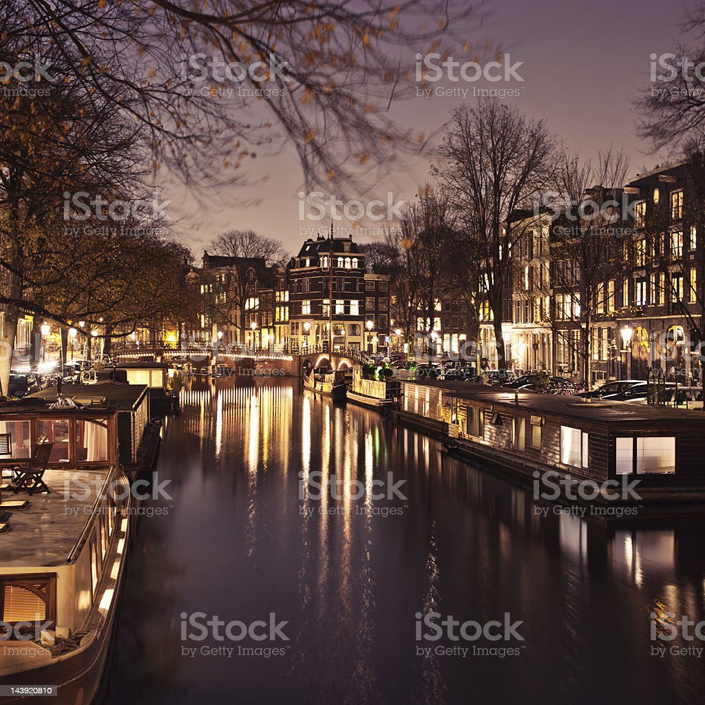 Amsterdam canal with houseboats at night stock photo