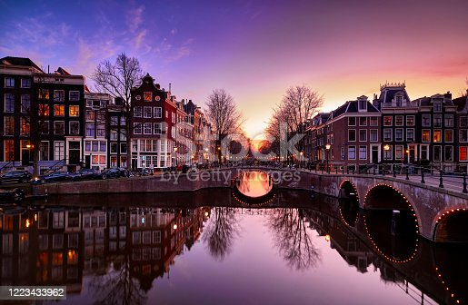 Amsterdam canals and typical canal houses in the old part of the city at dusk, the city lights are on. The streets are empty because of the lockdown, corona virus.