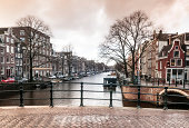 Amsterdam canals and typical boat-houses on a winter day. Cross-processing gives vintage image feeling.