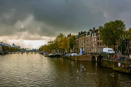 Amsterdam, Netherlands October 26, 2019: Amstel river of Amsterdam, capital of the Netherlands, on a cloudy day, dutch canal houses at right and bridge in the background