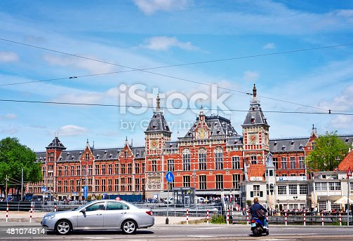Amsterdam, Netherlands - June 15, 2015: Amsterdam Centraal Station. Building exterior of Amsterdam Centraal and blue sky. Capital city of the Netherlands, central station or metro station.