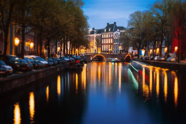 amsterdam-stadsgezicht met verlichte grachtenpanden en boten in de schemering - keizersgracht stockfoto's en -beelden