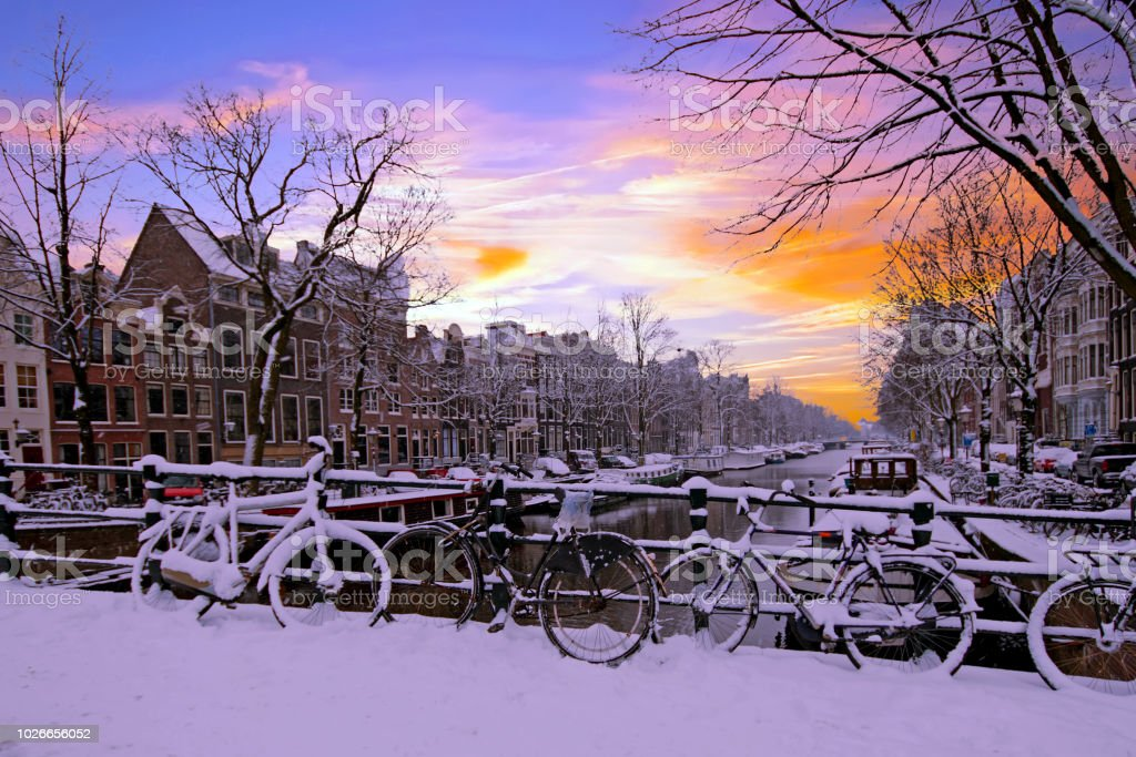 Amsterdam covered with snow  in winter in the Netherlands at sunset stock photo