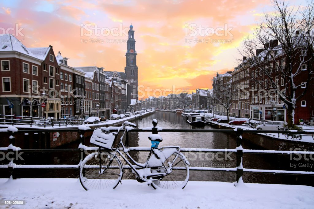 Amsterdam covered with snow with the Westerkerk in winter in the Netherlands at sunset stock photo