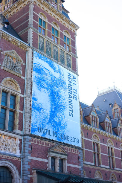 """Amsterdam, Holland: Facade of Rijksmuseum with Banner Amsterdam, Holland: Facade of the Rijksmuseum, built in 1885 and located in South Amsterdam; a blue banner advertises """"All the Rembrandts."""" rijksmuseum stock pictures, royalty-free photos & images"""