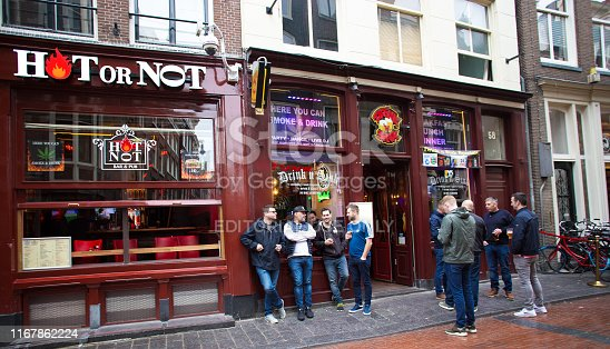 "Amsterdam, Holland: Male tourists stand chatting outside the bar ""Hot or Not"" at dusk in the Red Light District in downtown Amsterdam."