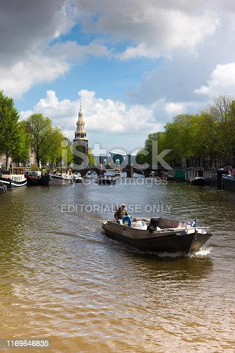 Amsterdam, Holland: Men in a motorboat on a canal in downtown Amsterdam in springtime, with the 17th-century Montalban Tower in the background and the NEMO Science Museum (by architect Renzo Piano) is in the distant background.
