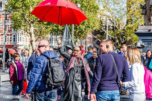 Amsterdam, Holland, September 2018 too many tourists visiting the city of Amsterdam proofs this long female guide with red umbrella and long leather jacket and sunglasses