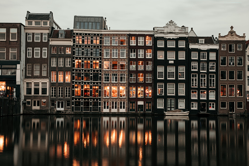 Amsterdam houses reflections at night on the water of the canal, Netherlands.