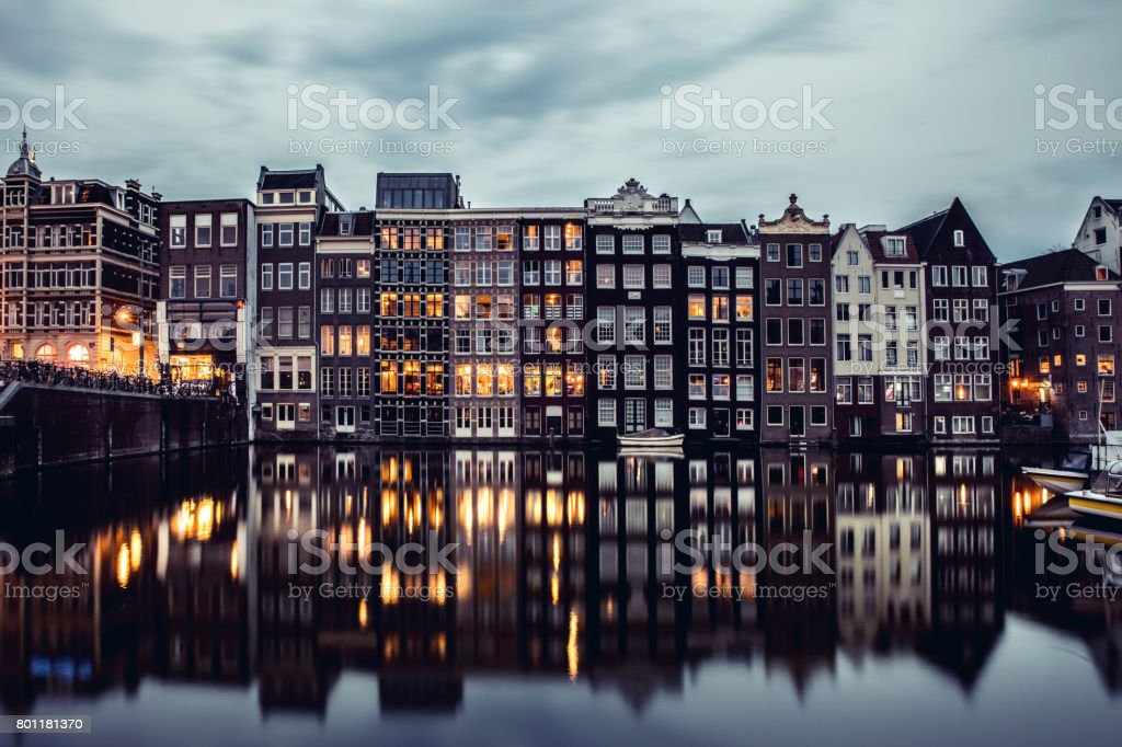 Amsterdam houses reflections at night on the water of the canal stock photo