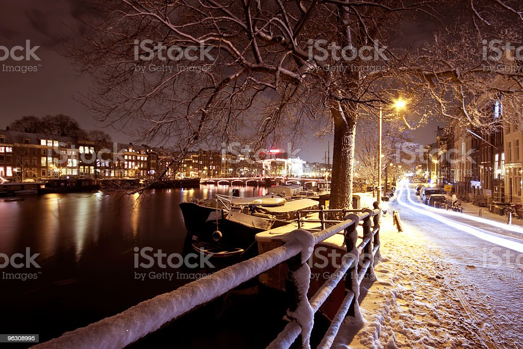Amsterdam in the Netherlands at night covered with snow stock photo