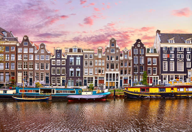 Amsterdam, Netherlands. Houseboats, dancing houses Amsterdam, Netherlands. Floating Houses and houseboats and boats at channels by banks. Traditional dutch dancing houses among trees. Evening autumn street above water pink sunset sky with clouds. canal stock pictures, royalty-free photos & images