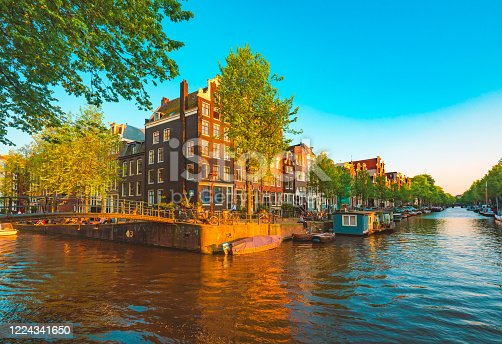 Amsterdam, Netherlands. Floating Houses, houseboats and boats at channels by banks. Traditional dutch dancing houses among trees. Evening autumn street