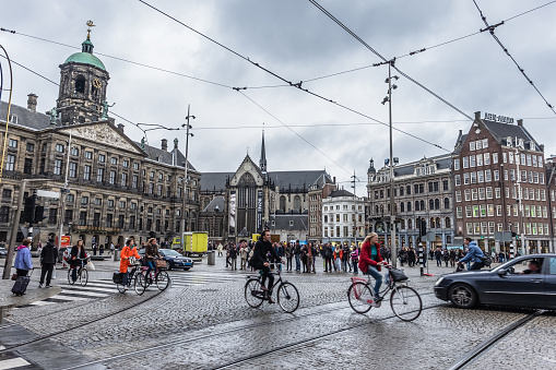 Amsterdam, Netherland - November 6, 2015: City of Amsterdam, this image is from the most hustle-bustle area called Dam Square in Amsterdam.Dam Square, or simply the Dam, is a town square in Amsterdam, the capital of the Netherlands. Its notable buildings and frequent events make it one of the most well-known and important locations in the city and the country. Dam Square lies in the historical center of Amsterdam. It links the streets Damrak and Rokin, which run along the original course of the Amstel River from Central Station to Muntplein and the Munttoren. The Dam also marks the endpoint of the other well-traveled streets Nieuwendijk, Kalverstraat and Damstraat. A short distance beyond the northeast corner lies the main red-light district: de Wallen. Local transport system in Amsterdam is outstanding and involves trams, trains, buses and local taxies. Bicycles are often the most preferred more of transport by locals and tourists.