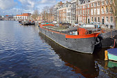Amsterdam, Netherlands -  March 2, 2015: Boats moored in the canals of Amsterdam