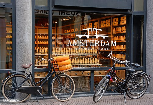 Amsterdam, The Netherlands - May 4th, 2016: Shop window of a cheese store in Amsterdam. Three bicycles parked in front of the store. Assortment of cheese visible through the window. Horisontal, outdoor image