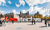 Amsterdam, Netherlands - May 03, 2016: Sign of 'I am Amsterdam' text sculpture with crowd of tourists front of the Rijksmuseum on Museumplein in Amsterdam. The red and white Iamsterdam sculpture is part of the marketing campaign to promote tourism in in the city.