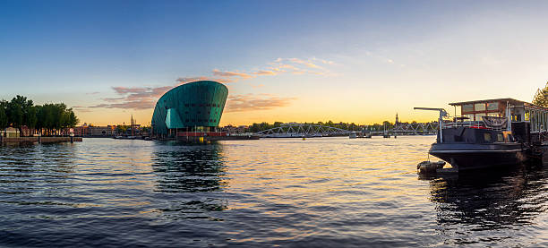 Amsterdam Skyline at Sunset Panorama Amsterdam, The Netherlands - September 26, 2015: Amsterdam Skyline at Sunset Panorama. Oosterdok harbor and Nemo Science Center. nemo museum stock pictures, royalty-free photos & images