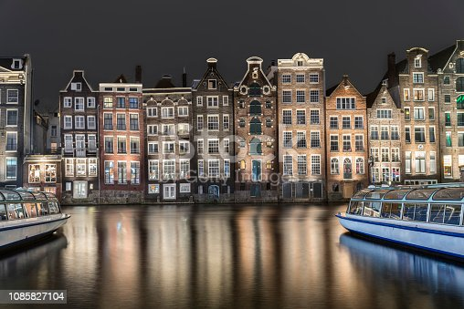 Set of neighboring buildings downtown Amsterdam, in front of a canal - Damrak. Night photograph with sightseeing boats.
