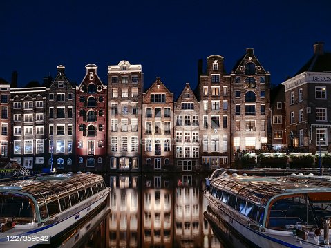 Set of neighbouring buildings downtown Amsterdam, in front of a canal - Damrak. Night photograph with sightseeing boats.