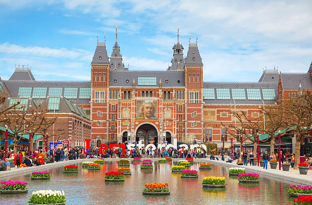 I Amsterdam slogan with crowd of tourists Amsterdam, Netherlands - April 16, 2015: I Amsterdam slogan with crowd of tourists in Amsterdam. Located at the back of the Rijksmuseum on Museumplein, the slogan quickly became a city icon. museumplein stock pictures, royalty-free photos & images
