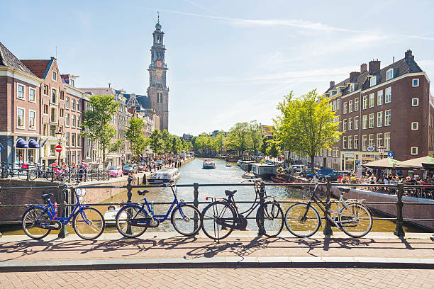 Amsterdam Summer A view over one of the many canals in Amsterdam. Bicycles, canals, boats and the Westerkerk in the back, making this photo completely and typical Amsterdam. canal stock pictures, royalty-free photos & images