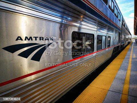 Amtrak two level passenger train stopped at San Jose Diridon station. Logo visible to the left, with the train and platform extending to the right.