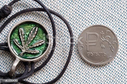 istock amulet with the image of marijuana and a rope to wear around the neck and a coin 1180000430