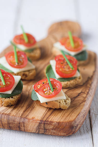 Amuse bouche? Bruschetta biscuits with tomato, spinach & cheese & a chive garnish - shallow dof amuse stock pictures, royalty-free photos & images