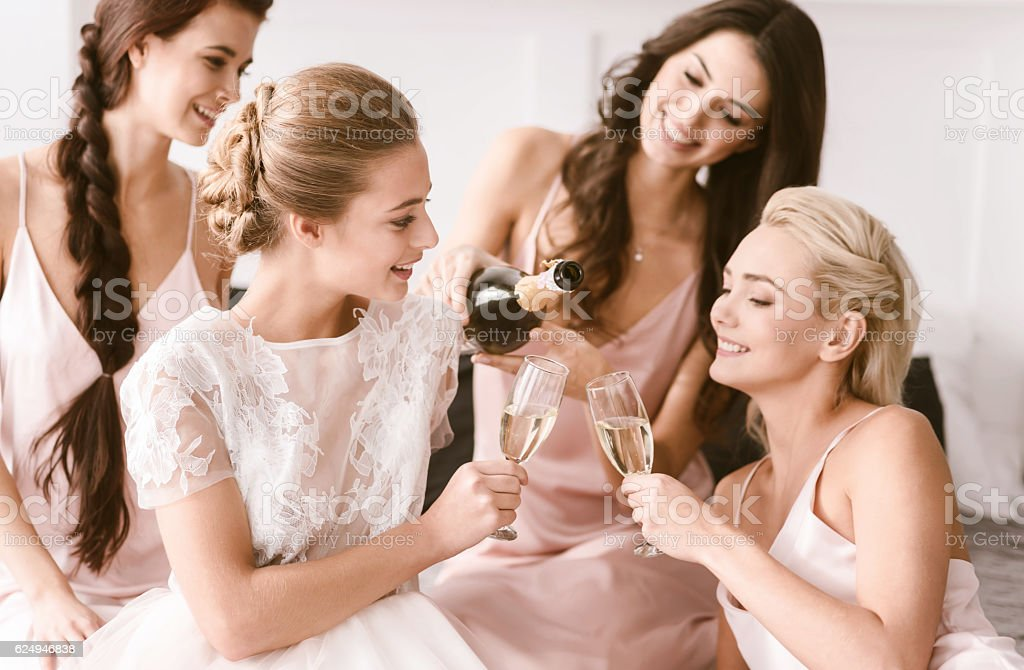 Amused bride and bridesmaids having hen party at home stock photo